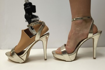 A prosthetic foot in a gold platform stiletto