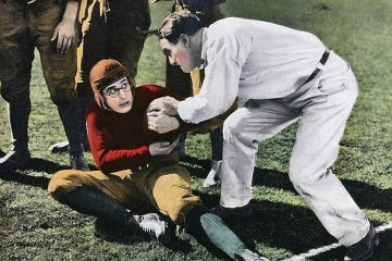 A colorized photo shows a man in a leather football helmet struggling with a referee to hold onto the ball