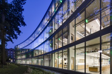 The image shows UTL's curved glass facade and the lab spaces inside