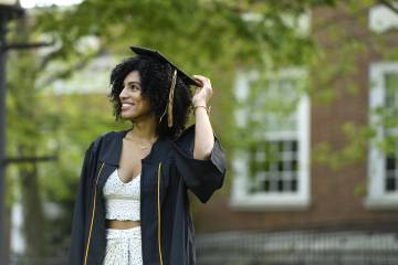 Student in Commencement regalia poses for a photo