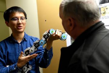 A student demonstrates a robotics project