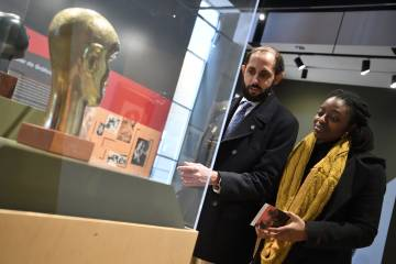Museum-goers look at sculptures