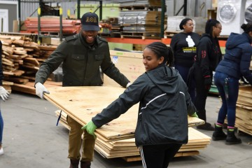 Students carry plywood boards
