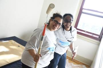 Volunteers paint a bedroom
