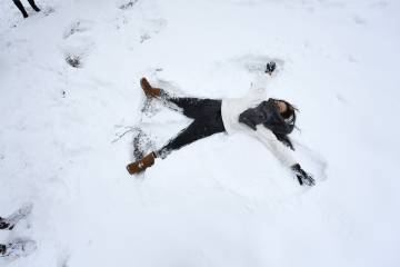 A female students makes a snow angel