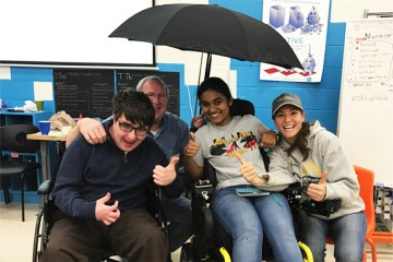 Members of team Rain Rain Go Away pose with their invention and a man who uses a wheelchair