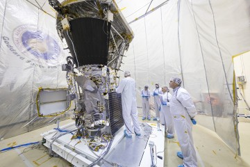 In a room tented in plastic, scientists in lab suits and hair nets inspect the Parker Solar Probe