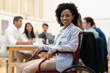 Woman in wheelchair working with colleagues around a table