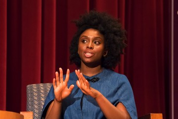 Chimamanda Ngozi Adichie on stage with crimson curtain backdrop