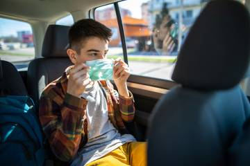 A teenager dons a mask in a car