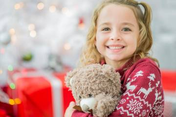 Smiling young girl hugging a teddy bear