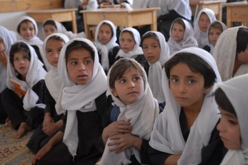 A group of children dressed in black dresses and draped in white head scarves sit in a classroom