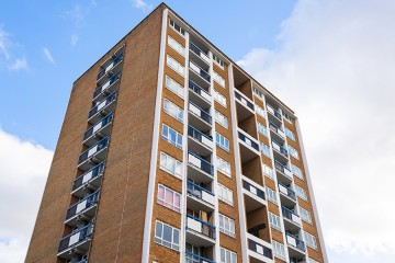 High-rise apartment building against a bright blue sky