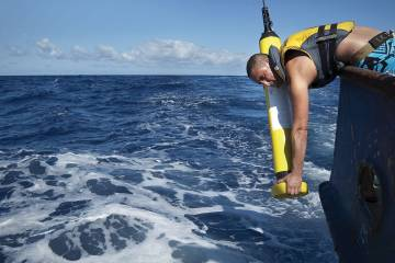 A man hangs over the edge of a boat, deploying an Argo float into the ocean