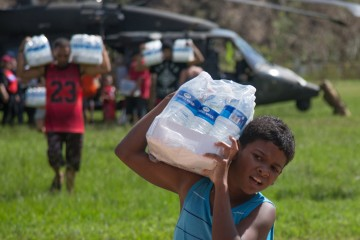 A boy carries a case of water