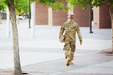 A student in a military uniform walks across a college campus