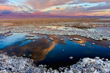 Large salt flat with cloud reflected in blue water and pink mountains on the horizon