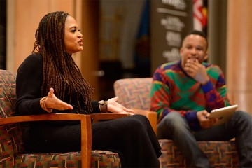 Ava DuVernay sits in a chair on stage