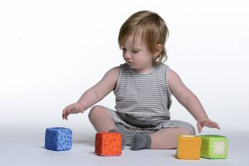 A baby selects a toy from a selection of toys in front of him