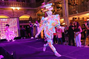 Ballroom performer in book costume struts on the catwalk