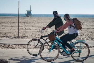 A couple rides bikes near a beach