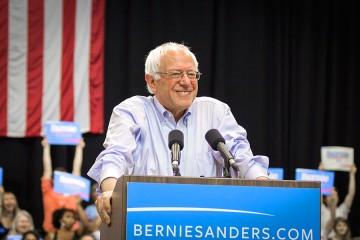 Bernie Sanders smiles at podium with US. flag backdrop