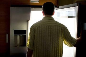 Man is silhouetted as he stands in front of open refrigerator door