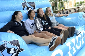 Four students sit in an inflatable chair holding a Blue Jay shield