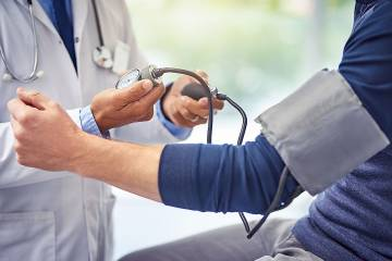 Doctor taking a man's blood pressure reading