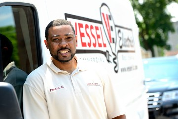 Renard Gardner leans against his white work van