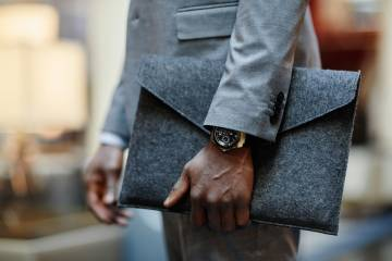 A man in a suit holds a portfolio