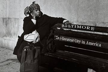 A woman sits on a bench in Baltimore