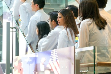Medical students in white coats watch an announcement of a new cancer immunotherapy institute