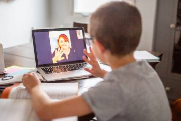 Young boy waving to a teacher on his laptop screen