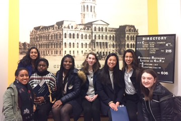 A group of 8 students pose for a photo in front of an image of City Hall