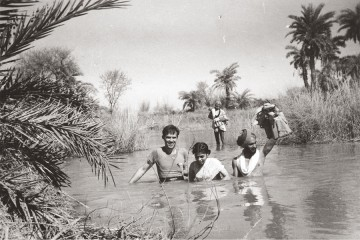 Black and white image features Carl Taylor and three guides crossing a deep river in India