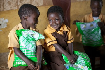 Two small children smile and hold bright green bags