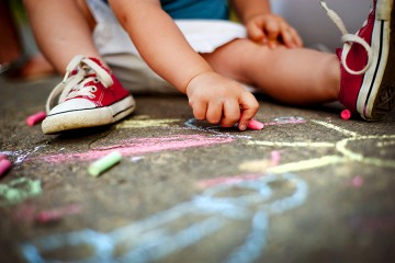 Young child colors on sidewalk with chalk