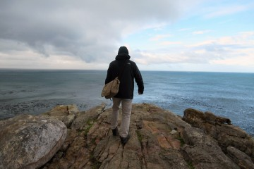 A man stands with his back to the camera facing out over the sea