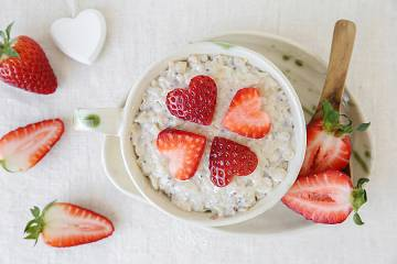 Heart-shaped strawberry slices atop a bowl of oatmeal