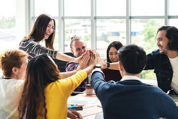 Group of multiethnic diverse people high-five, laughing and smiling together in a meeting in the office