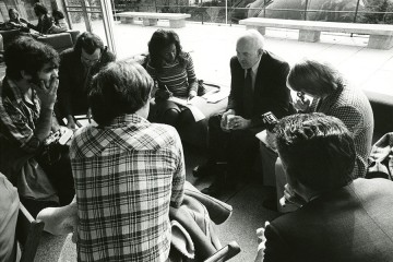 Black and white photo of James Coleman speaking with a small group of reporters