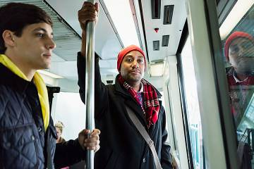 Man holds upright pole on a city bus