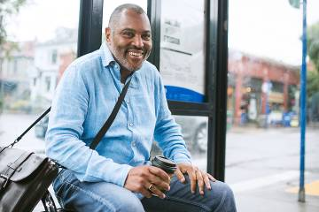 Middle-aged man sitting at a bus stop