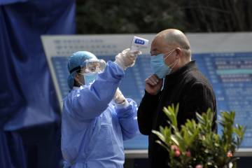 A health worker checks a man's temperature before he enters a hospital in China