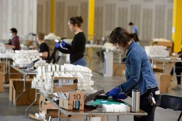 Volunteers assemble face shields in a warehouse