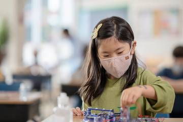 Young girl wearing a medical mask and playing with toys in a day care setting