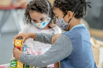 Toddler girl and boy playing at daycare while wearing masks