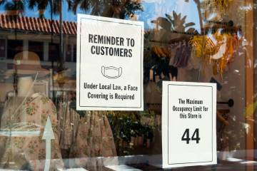 A sign requiring masks and stating an occupancy limit is displayed on a shop window
