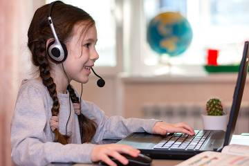 Young girl wearing headphones and working on a laptop